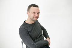 Junger erwachsener europäischer Mann sitzt auf Stuhl Lizenzfreie Stockbilder