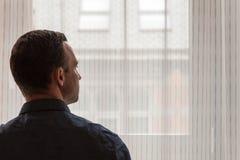 Junger erwachsener europäischer Mann steht nahes Fenster lizenzfreie stockfotos