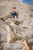 Junger erwachsener kletternder Felsen gesichert im Seil Lizenzfreie Stockfotografie