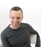 Junger erwachsener lachender Mann sitzt auf einem Stuhl Stockfotografie