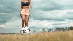 Junger erwachsener Mädchenabschluß, der oben den Fußball oder Fußball, einen Ball mit ihrer Knie schönen Brunettefrau in tretend