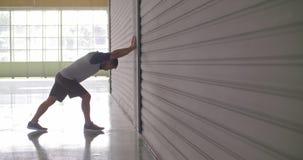 Junger erwachsener Mann, der das Ausdehnen während des Eignungssporttrainings aufwärmt Weicher Fokus Industrielles städtisches Tr stock video footage