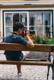 Junger erwachsener Mann, der die Fotos zurück sitzen auf Bank macht stockfotos