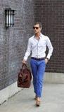 Junger erwachsener Mann, der ein Kleidersack-Gehen hält stockfoto