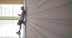Junger erwachsener Mann, der Spurhaltungsapp des Smartphone während des Eignungssporttrainings verwendet Industrielles städtische lizenzfreie stockfotos