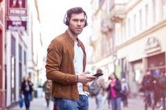 Junger erwachsener Mann-hörende Musik auf Smartphone und Kopfhörer auf der Straße zur Sommerzeit stockfotografie