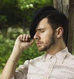 Junger erwachsener Mann mit dem Kappenstillstehen im Freien Stockbild
