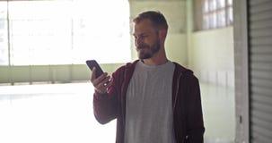 Junger erwachsener Mann mit mit Kapuze Sweatshirt unter Verwendung des Smartphone während des Eignungssporttrainings Industrielle stock video