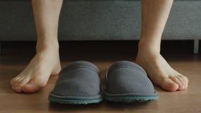 Junger erwachsener Mann sitzt auf einem Sofa nahe Pantoffel - Füße gerade stockfoto