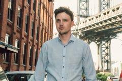 Junger erwachsener Unternehmermann, der auf Stadtstraße von New York City geht lizenzfreies stockfoto