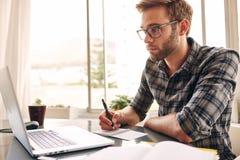 Junger erwachsener Verfasser, der seinen Notizbuchschirm betrachtet Stockfotografie