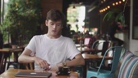 Junger Essengummi nach Tasse Kaffee, gesundes Zahnkonzept, moderner Arbeitsplatz, der im Café sitzt Offener Laptop herein stock video footage
