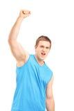 Junger euphorischer Sportler mit der angehobenen Hand Glück gestikulierend Stockbilder