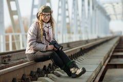 Junger europäischer Frauenphotograph, der die erste Frühlingssonne erforscht Eisenbahnbrücke der Vorstadtstandorte genießt Stockfoto