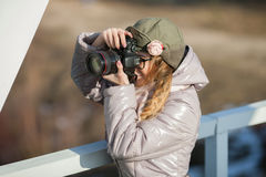 Junger europäischer Frauenphotograph, der die erste Frühlingssonne erforscht Eisenbahnbrücke der Vorstadtstandorte genießt Lizenzfreie Stockfotografie