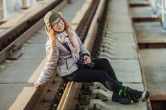 Junger europäischer Frauenphotograph, der die erste Frühlingssonne erforscht Eisenbahnbrücke der Vorstadtstandorte genießt Stockfotografie