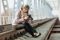 Junger europäischer Frauenphotograph, der die erste Frühlingssonne erforscht Eisenbahnbrücke der Vorstadtstandorte genießt Lizenzfreies Stockfoto