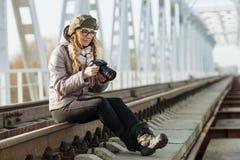 Junger europäischer Frauenphotograph, der die erste Frühlingssonne erforscht Eisenbahnbrücke der Vorstadtstandorte genießt Lizenzfreie Stockfotos