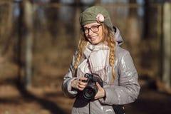 Junger europäischer Frauenphotograph, der die erste Frühlingssonne erforscht Vorstadtstandorte genießt Stockfotos
