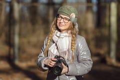 Junger europäischer Frauenphotograph, der die erste Frühlingssonne erforscht Vorstadtstandorte genießt Lizenzfreie Stockfotos