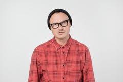 Junger europäischer Mann im roten Hemd machte Stirnrunzeln und Blicke sullenly unzufrieden lizenzfreie stockbilder