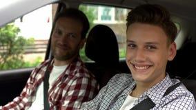 Junger Fahrer und sein Vater, die in Kamera, jugendlich erhaltener Führerschein lächelt stockbilder