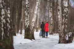 Junger Familienweg im Winterholz Elternteilziehen Stockfoto