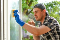 Junger Fensterputzer mit einem Sprayreinigungsmittel auf Glas Stockfotografie