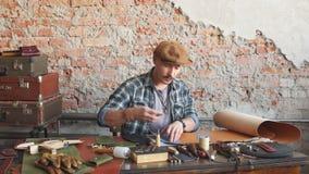 Junger fleißiger Mann, der mit Leder unter Verwendung des In Handarbeit machens von Werkzeugen arbeitet stock video footage