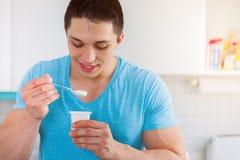 Junger Fleisch fressender Jogurt in der gesunden Küche isst Frühstück lizenzfreie stockfotografie