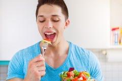 Junger Fleisch fressender Salat in der gesunden Küche essen strengen Vegetarier stockfotos