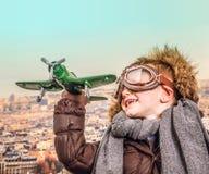 Junger Flieger, der mit Spielzeugflugzeug spielt stockfotografie