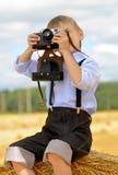 Junger Fotograf, der auf Heu sitzt Stockbilder