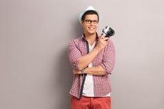 Junger Fotograf, der eine Kamera hält Stockfotografie