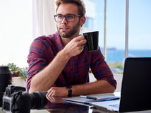 Junger Fotograf, der Kaffee an seinem Arbeitsschreibtisch hält Stockbilder