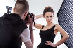 Junger Fotograf, der mit Berufsmodell arbeitet Stockbild