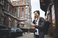Junger Fotograf, der reisen mag, überprüft seinen gegenwärtigen Standort während des Telefonanrufs stockfotografie