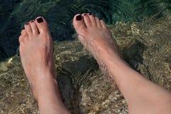 Junger Frau manicured Füße im Wasser lizenzfreies stockbild