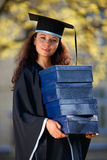 Junger Frauabsolvent mit Stapel Kästen stockbild