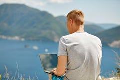 Junger Freiberufler, der Laptop verwendet Lizenzfreie Stockfotos