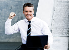 Junger freudig erregt Unternehmensmann mit Laptop Lizenzfreie Stockfotografie