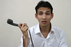 Junger frustrierter Mann mit Telefon Stockbild