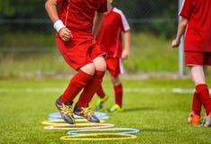 Junger Fußball-Spieler, der auf der Neigung übt Fußball-Fußball Equpment Dynamische springende Fußball-Praxis stockfotografie