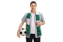 Junger Fußballfan mit einem Schal und einem Fußball Stockfoto