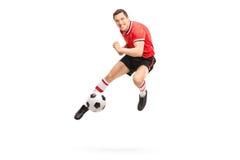Junger Fußballspieler, der einen Ball tritt Stockbild