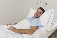 Junger geduldiger Mann, der am Krankenhausbett stillsteht das müde Schauen trauriges und deprimiertes besorgtes liegt Lizenzfreie Stockbilder