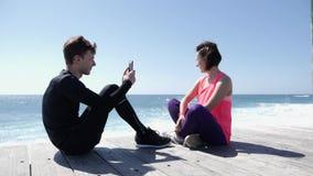 Junger geeigneter Mann, der auf dem Strand macht Fotos seiner Freundin mit dem Telefon sitzt Starke Wellen, die gegen die Felsen  stock video footage