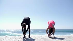 Junger geeigneter Mann und Frau, die Übungen an einem sonnigen Tag auf dem Strand ausdehnend tut stock video