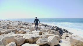 Junger geeigneter Sportler, der ?ber die Felsen auf einem Strand mit den starken Meereswogen das Klippen- und Wasserspritzen schl stock video