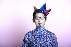 Junger Geeky asiatischer Mann, der viele Parteihüte trägt  Lizenzfreie Stockfotos